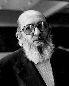 Photo portrait of a balding middle-aged man with a medium-length white beard, wearing large glasses and a suit.