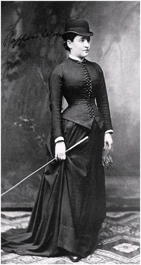 A woman in a floor-length dress with long sleeves. She holds a long white stick.