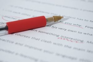 A red pen sits on top of paper that has been corrected in red pen