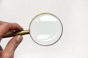 A hand holding a magnifying glass.