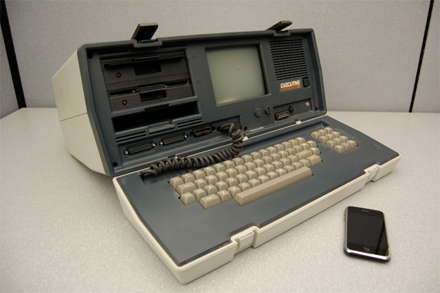 A large, old computer (roughly 2 feet by 1 foot large) with an iphone sitting next to it