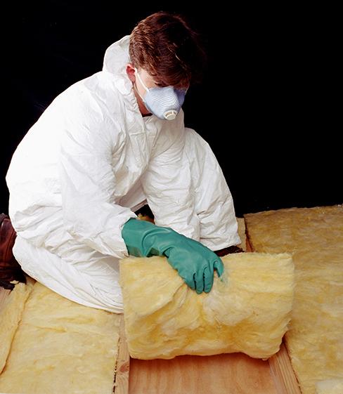 Photograph of a person handling a fiberglass batt.