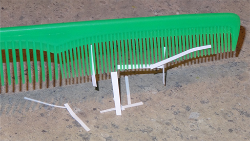 A photograph of thin strips of paper stuck to a plastic comb.