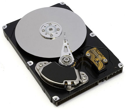 Photo shows the inside of a hard disk drive. The silver disk contains the information, whereas the thin stylus on top of the disk reads and writes information to the disk.