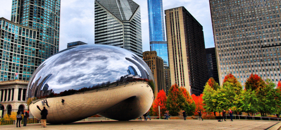 Photo shows a gigantic bean shaped structure in a plaza that is lined with trees and tall buildings. The structure's concave underside is tall enough for people to walk under. The shiny surface of the structure reflects and distorts the image of a cloudy sky, the floor of the plaza, and the buildings and trees surrounding the structure.
