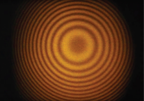 Picture shows a photograph of the fringes produced with a Michelson interferometer. Fringes are visible as alternating dark and light circles.