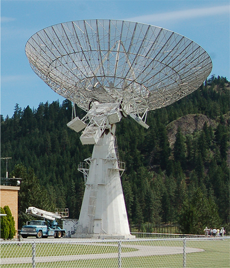 Photograph of a large dish antenna on top of a conical pillar.