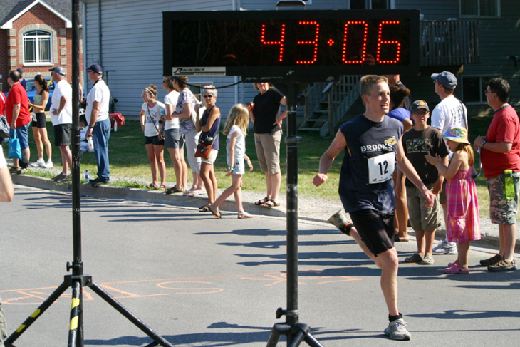 A photo of the finish of a foot race with the time �43:06� shown for the racer crossing the finish line.
