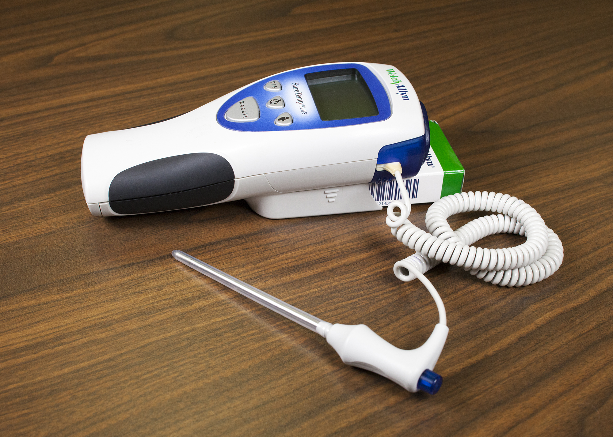 Oral thermometer that shows the blue end on the device and the probe with probe cover on.
