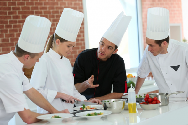 Four chefs in tall white hats prepare a meal together in a room with brick walls and a large window.