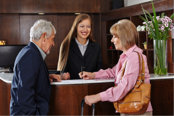 A couple checks into a hotel. Behind the front desk is a smiling woman.
