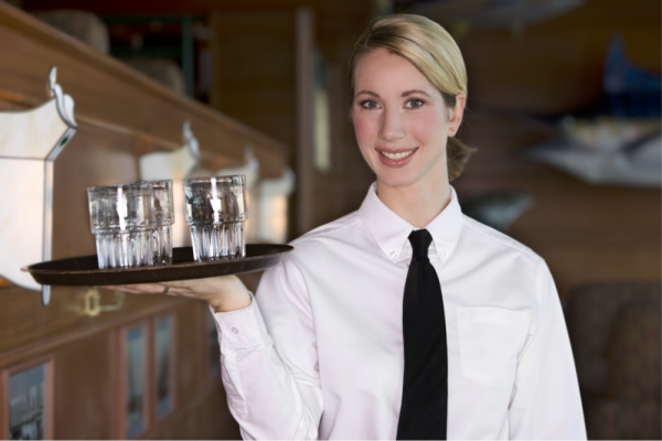 A female server wearing a white shirt and black tie bears a tray of glasses and smiles.