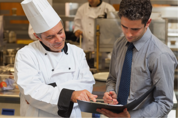 A chef confers with a man in a shirt and tie holding a file. Both men are focused on the file.