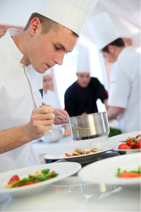A chef drizzles sauce over a plate. In the background, more chefs work.