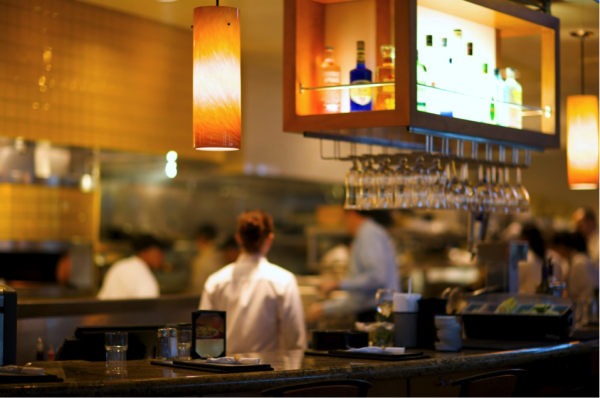A restaurant bar with soft lighting and glasses hanging upside down above the counter.