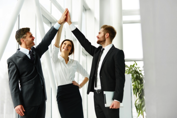 Three office workers raise their hands in a three-way high five.