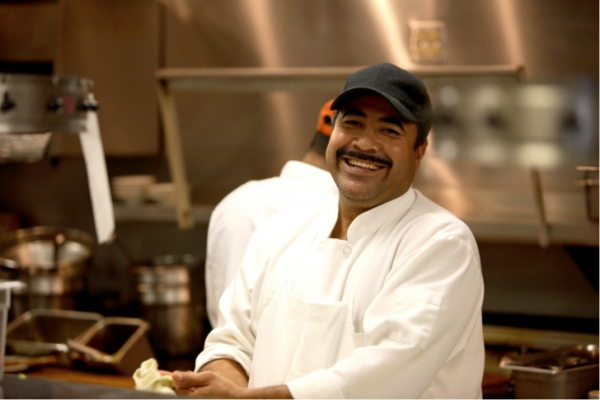 A chef in an industrial kitchen wears a black cap and a wide smile.
